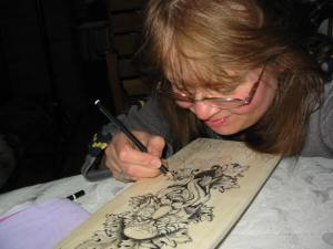 Vikki Soros working on a paddle artwork donation for the Sudbury Theater Center